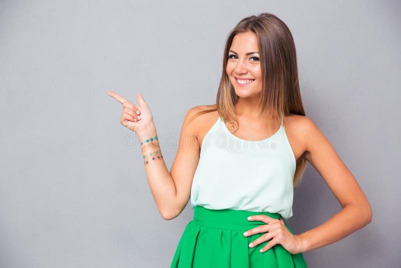 Uśmiechnięta ładna kobieta wskazuje palcowy oddalonego zdjęcie stock