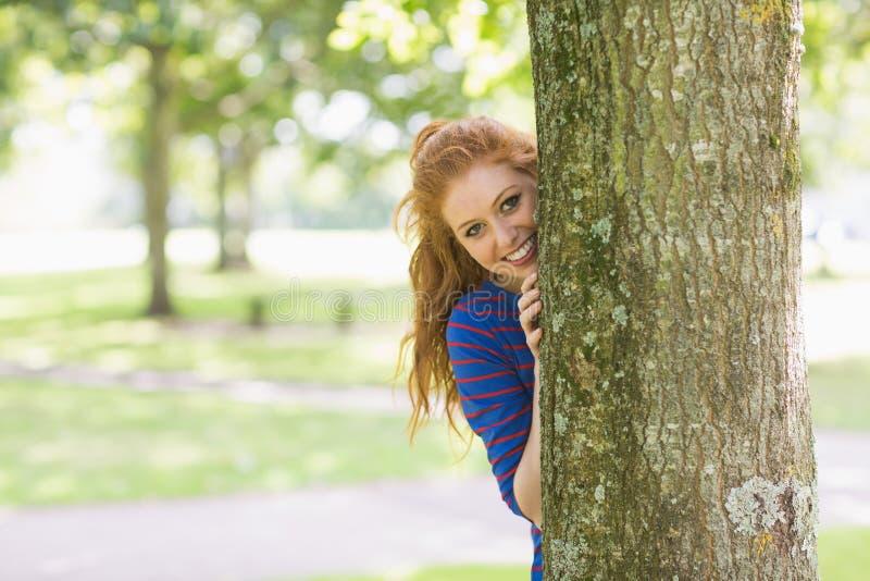 Uśmiechnięta ładna rudzielec chuje za drzewem zdjęcia stock