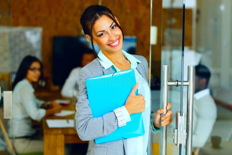 Uśmiechnięta śliczna bizneswoman pozycja z falcówką obrazy stock
