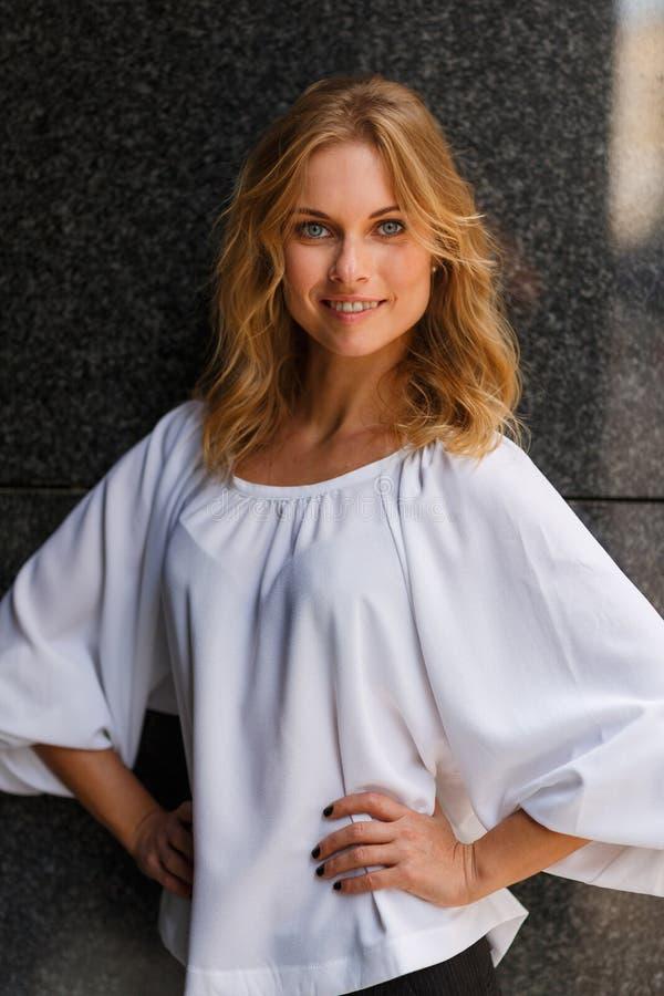 Uśmiechnięta śliczna blond dziewczyna w przyroscie pozuje outdoors fotografia royalty free
