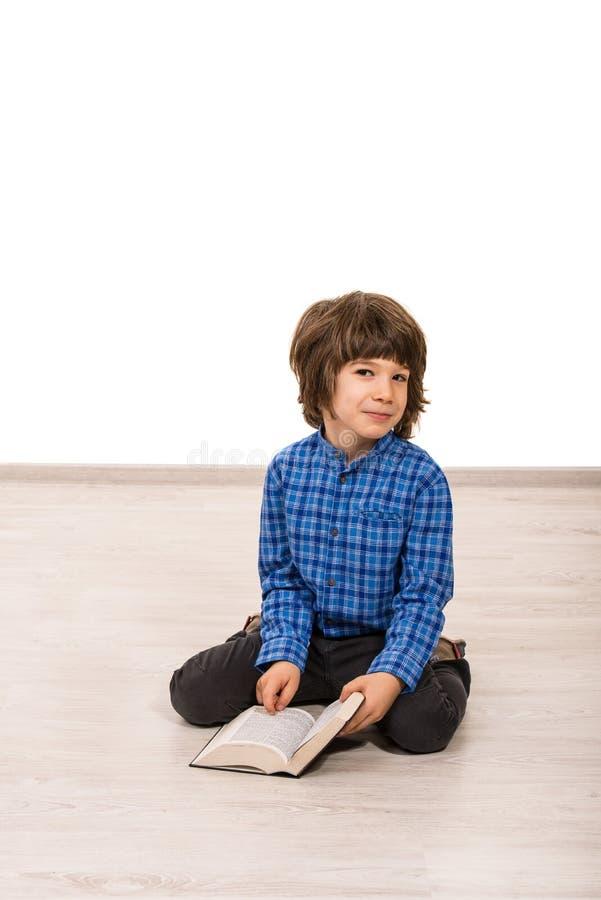 Uśmiechnięta śliczna chłopiec z książką zdjęcie royalty free