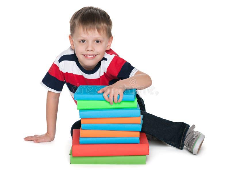 Uśmiechnięta śliczna chłopiec z książkami zdjęcie royalty free