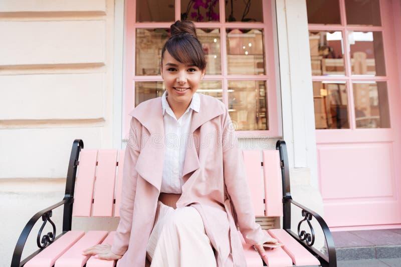 Uśmiechnięta śliczna dziewczyna w różowym kurtki obsiadaniu na ławce obrazy royalty free