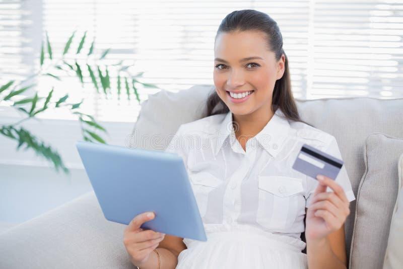 Uśmiechnięta śliczna kobieta kupuje online używać jej pastylka komputer osobistego zdjęcia stock