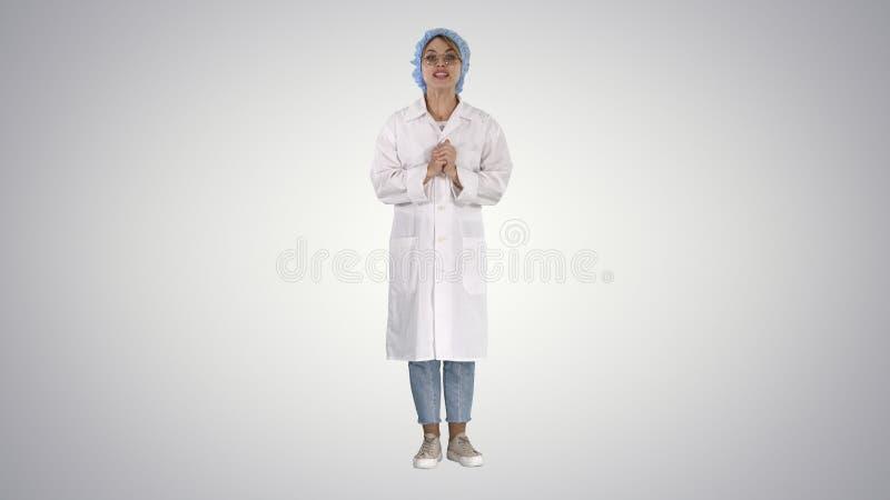 Uśmiechnięta śliczna lekarz medycyny kobieta opowiada kamera na gradientowym tle obrazy royalty free