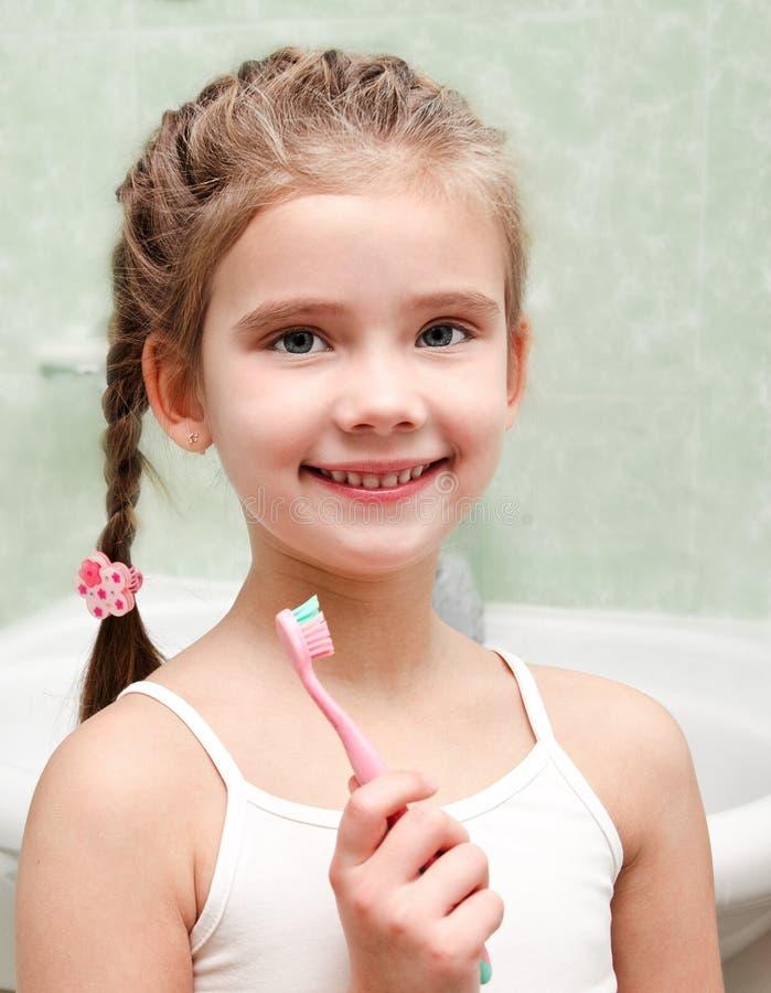 Uśmiechnięta śliczna mała dziewczynka szczotkuje zęby fotografia stock