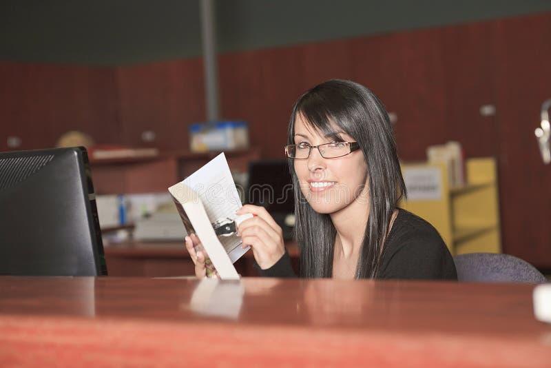 Uśmiechnięta żeńska bibliotekarka trzyma książkową pozycję obrazy stock