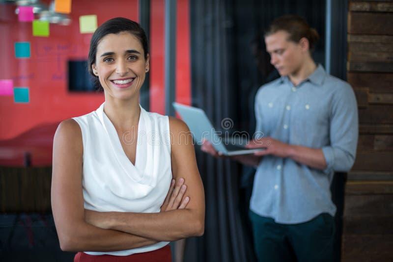 Uśmiechnięta żeńska dyrektor wykonawczy pozycja z rękami krzyżował w biurze zdjęcia stock