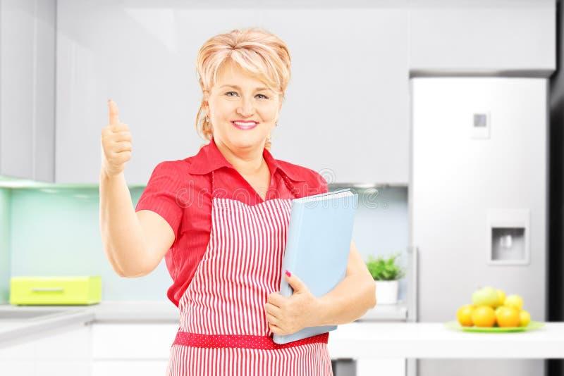 Uśmiechnięta żeńska kuchenka trzyma książkę kucharska i daje kciukowi up zdjęcie stock