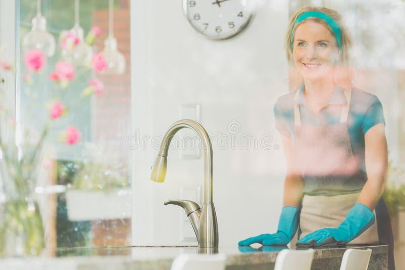 Uśmiechnięta żona czyści odpierającego wierzchołek fotografia stock