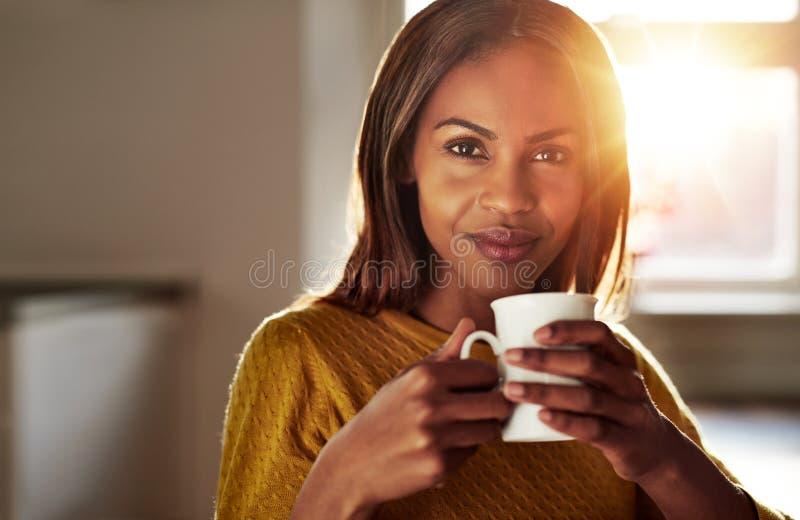 Uśmiechnięta życzliwa młoda murzynka pije kawę obraz stock
