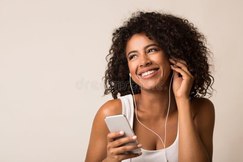 Uśmiechnięta afroamerykańska kobieta słucha muzykę w earbuds zdjęcia stock