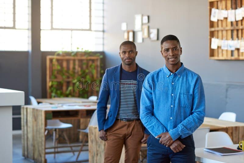 Uśmiechnięta Afrykańska biznesmen pozycja z kolegą w biurze obraz stock