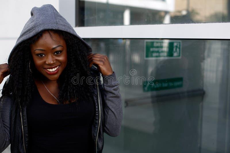Uśmiechnięta Afrykańska kobieta jest ubranym kapturzastego wierzchołek zdjęcia royalty free
