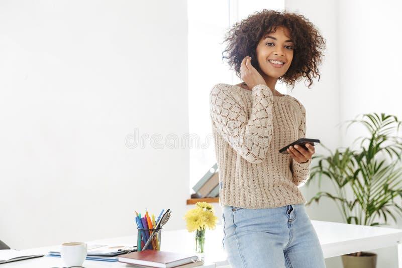 Uśmiechnięta afrykańska kobieta jest ubranym w przypadkowych ubraniach trzyma smartphone fotografia stock