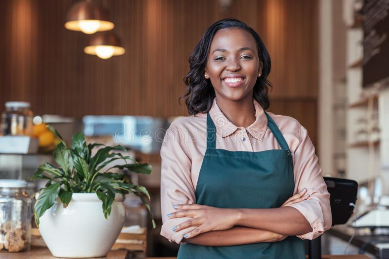 Uśmiechnięta Afrykańska przedsiębiorca pozycja przy kontuarem jej kawiarnia zdjęcia royalty free