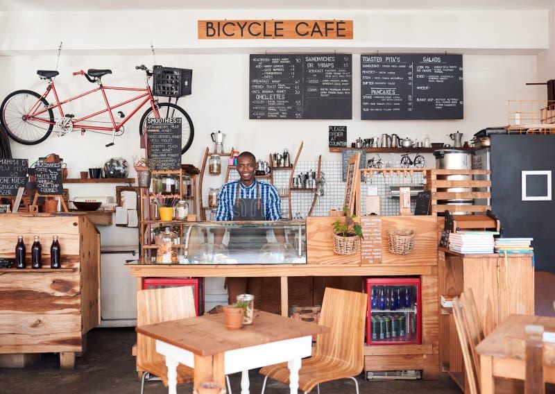 Uśmiechnięta Afrykańska przedsiębiorca pozycja za kontuarem jego kawiarnia fotografia royalty free
