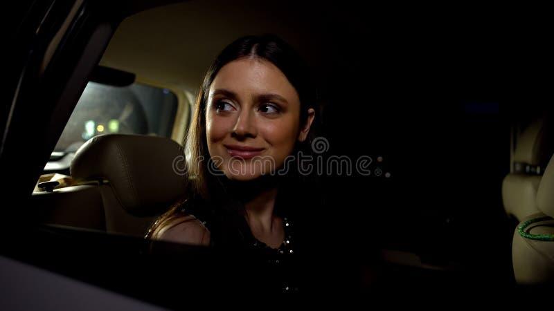 Uśmiechnięta aktorka witająca ludzi z samochodu, przyjeżdżająca do ważnej partii nagród fotografia royalty free