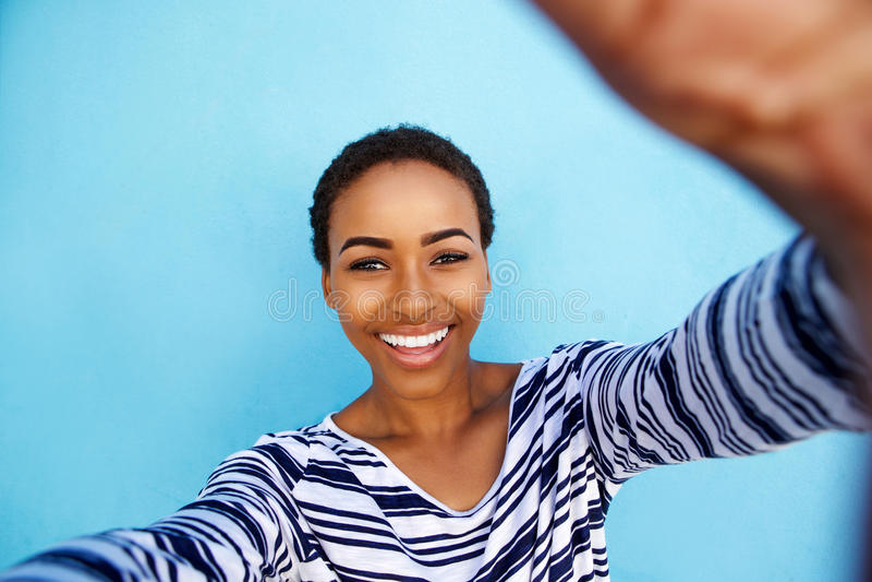 Uśmiechnięta amerykanin afrykańskiego pochodzenia kobieta bierze selfie przeciw błękit ścianie obraz royalty free
