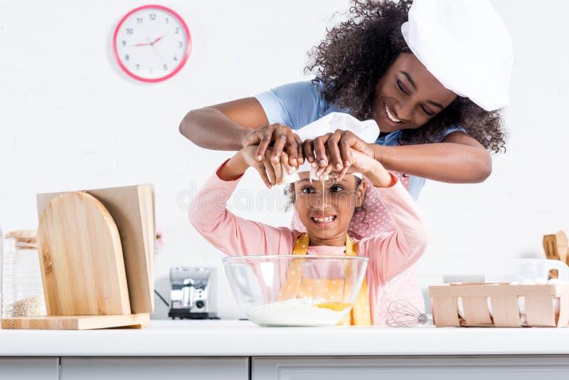 uśmiechnięta amerykanin afrykańskiego pochodzenia matka, córka w szefów kuchni kapeluszach stawia jajka w puchar wpólnie i obrazy stock
