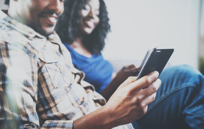 Uśmiechnięta amerykanin afrykańskiego pochodzenia para relaksuje wpólnie na leżance Młody murzyn i jego dziewczyna używa smartpho zdjęcia royalty free