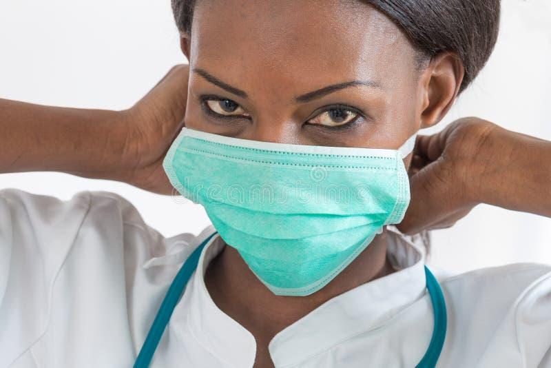 Uśmiechnięta amerykanin afrykańskiego pochodzenia pielęgniarka przy szpitalną pracy stacją na białym tle obraz royalty free