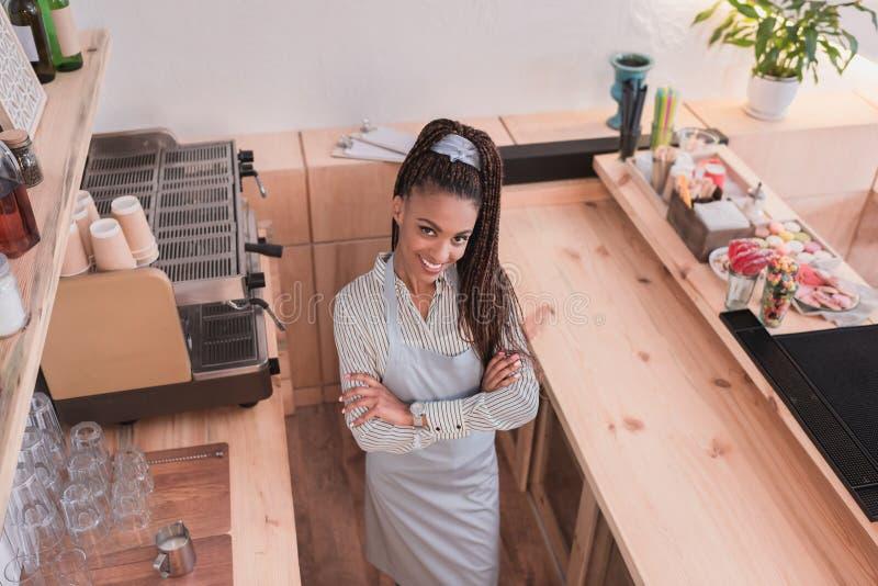 Uśmiechnięta amerykanina afrykańskiego pochodzenia barista pozycja z rękami krzyżować, za kontuarem przy kawą obrazy royalty free