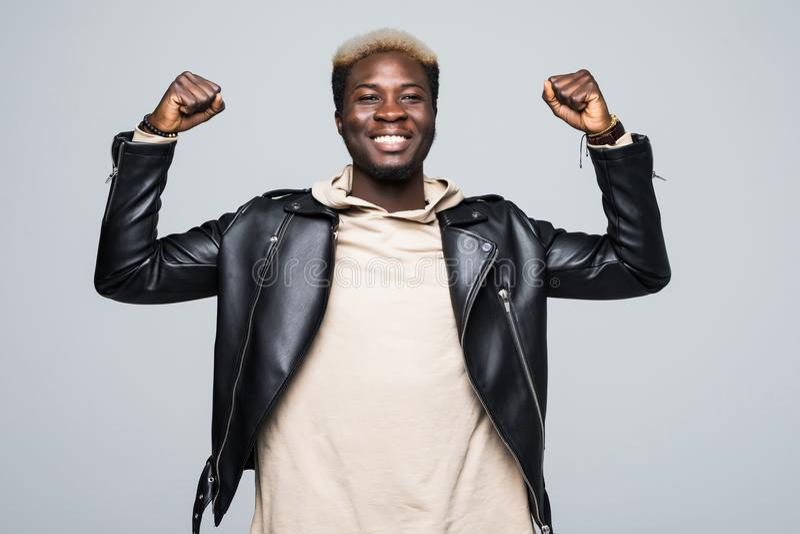 Uśmiechnięta amerykanina afrykańskiego pochodzenia młodego człowieka pozycja i odświętność sukces odizolowywający na szarość zdjęcie stock