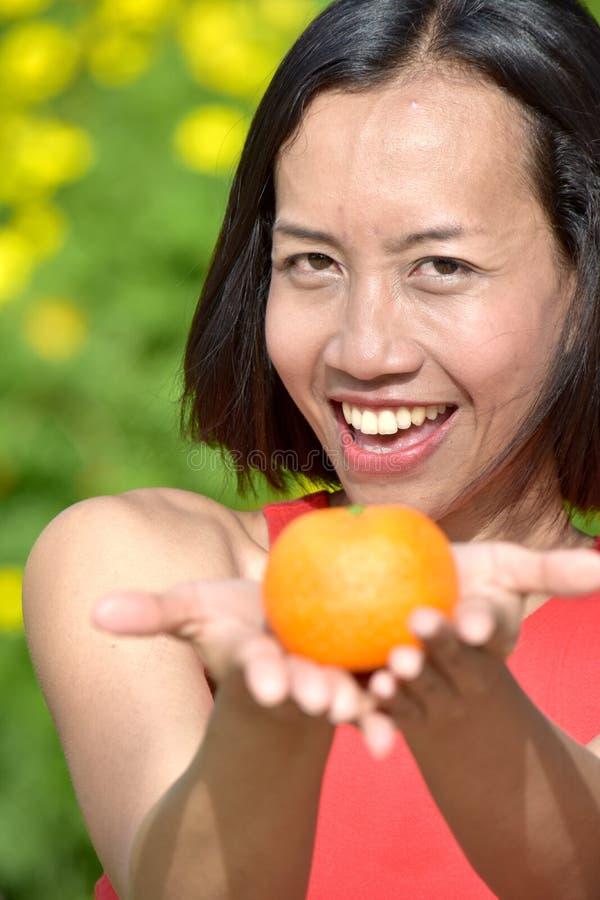 Uśmiechnięta Atrakcyjna Różnorodna kobieta Z pomarańcze fotografia stock