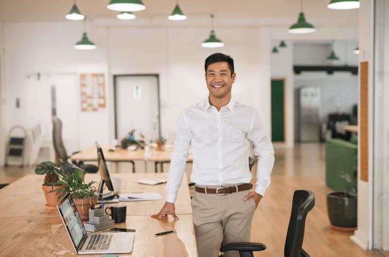 Uśmiechnięta Azjatycka biznesmen pozycja jego biurkiem w biurze zdjęcie stock