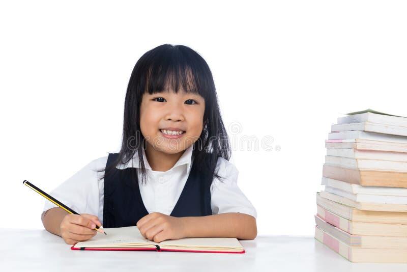Uśmiechnięta Azjatycka Chińska mała dziewczynka jest ubranym mundurka szkolnego studyin zdjęcie royalty free