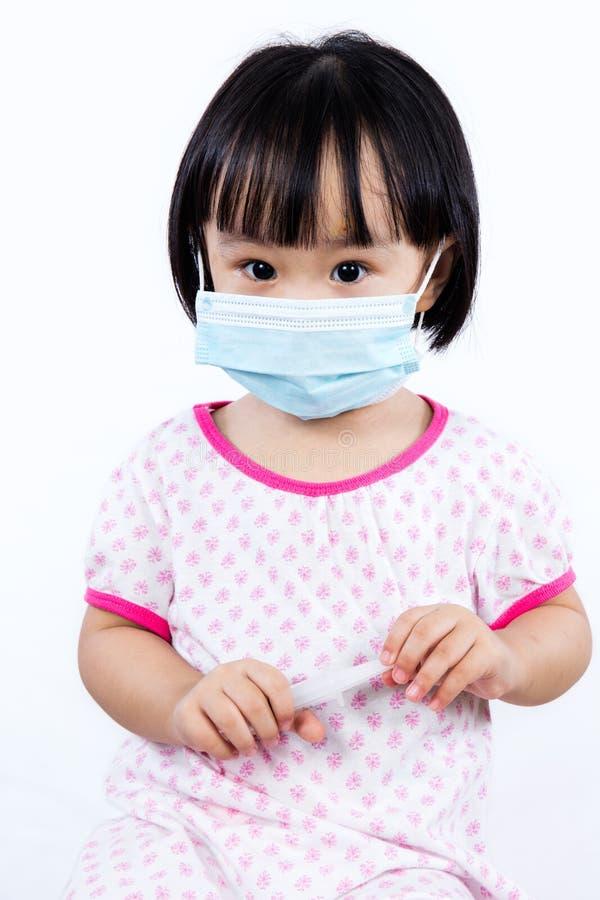 Uśmiechnięta Azjatycka Chińska mała dziewczynka Jest ubranym ochrony maskę zdjęcie stock