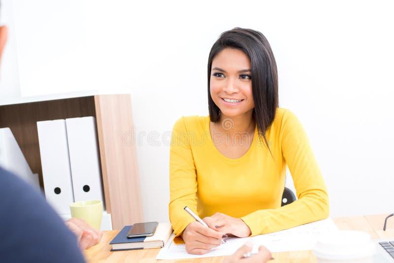 Uśmiechnięta Azjatycka kobieta jest ubranym przypadkową żółtą koszulkę w spotkaniu zdjęcia royalty free