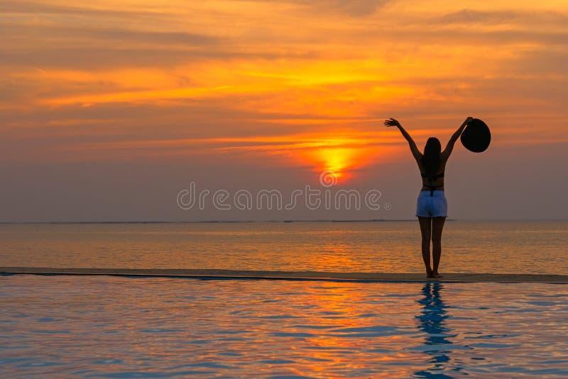 Uśmiechnięta azjatykcia kobieta szczęśliwa w duży kapeluszowy relaksować na pływackim basenie, podróży i plaży w zmierzchu, blisk zdjęcie stock