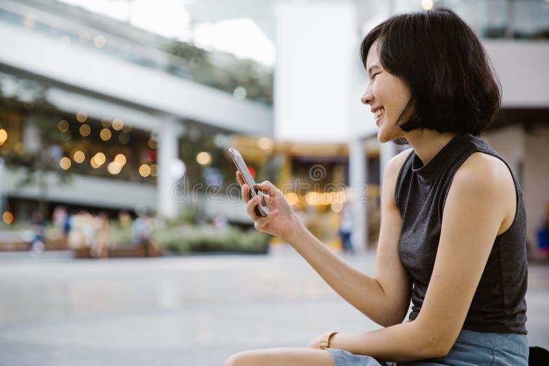 Uśmiechnięta azjatykcia kobieta używa Mobil telefon sms fotografia stock