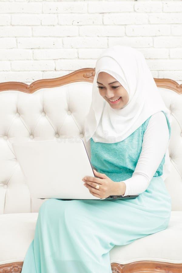 Uśmiechnięta azjatykcia młoda kobieta jest ubranym hijab obsiadanie na kanapie podczas gdy wo fotografia royalty free