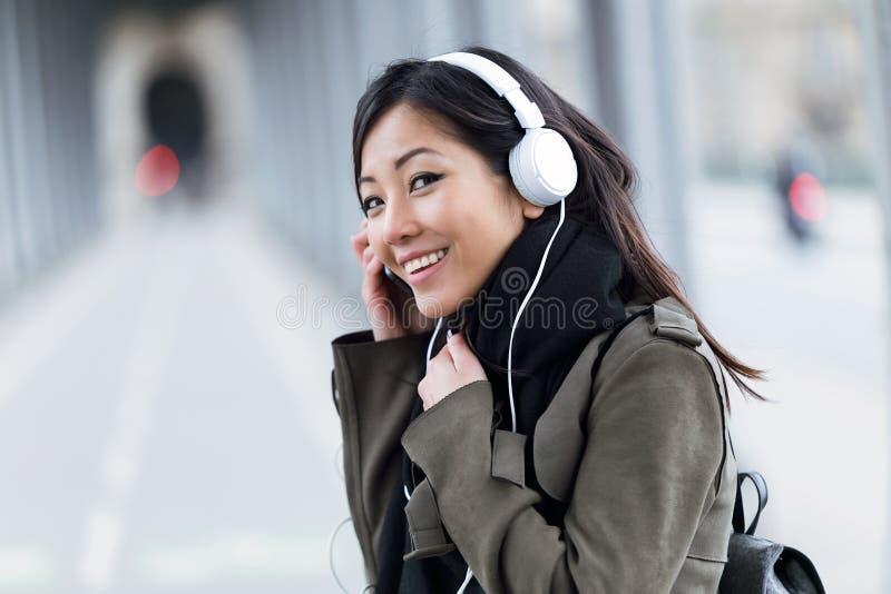 Uśmiechnięta azjatykcia młoda kobieta słucha muzyczna i patrzeje kamera w ulicie zdjęcie stock