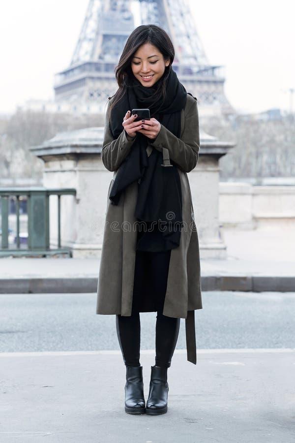 Uśmiechnięta azjatykcia młoda kobieta używa jej telefon komórkowego przed wieżą eifla fotografia stock