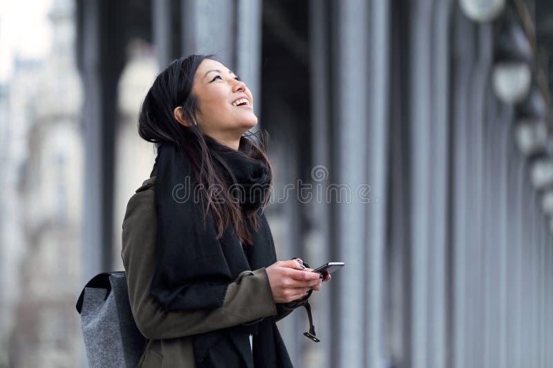 Uśmiechnięta azjatykcia młoda kobieta używa jej telefon komórkowego w ulicie obrazy royalty free