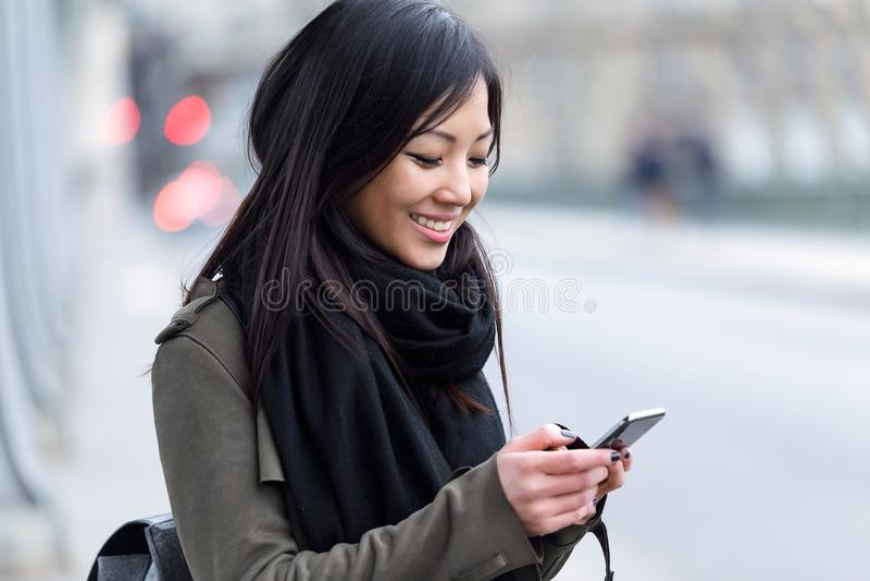 Uśmiechnięta azjatykcia młoda kobieta używa jej telefon komórkowego w ulicie zdjęcia stock