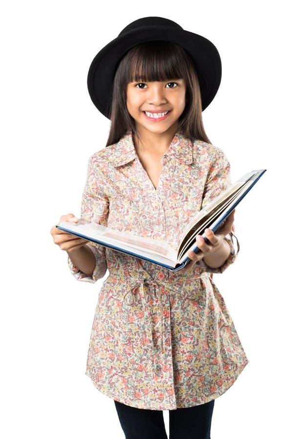 Uśmiechnięta azjatykcia mała dziewczynka z książką w ręce zdjęcie royalty free