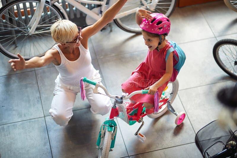 Uśmiechnięta babcia i dziewczyna wybiera bicykl i hełmy w rowerze robimy zakupy fotografia stock
