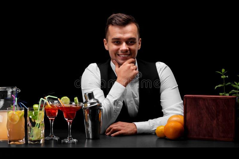 Uśmiechnięta barman pozycja za prętowym kontuarem na czarnym tle Restauraci usługa i rozrywki pojęcie zdjęcia royalty free