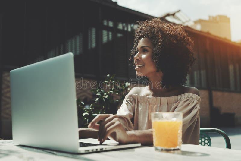 Uśmiechnięta biracial kobieta w ulica barze z sokiem i laptopem zdjęcia stock