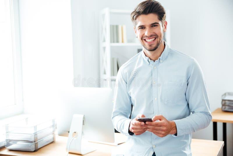 Uśmiechnięta biznesmen pozycja i używać telefon komórkowy w biurze fotografia royalty free