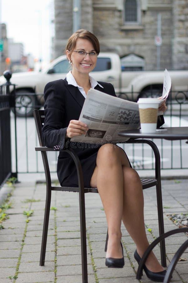 Uśmiechnięta biznesowa kobieta czyta gazetę przy plenerowym sklep z kawą zdjęcie royalty free
