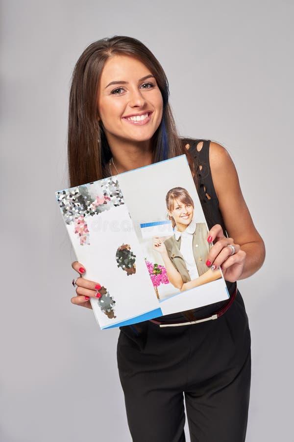 Uśmiechnięta biznesowa kobieta pokazuje reklamową broszurkę obrazy royalty free
