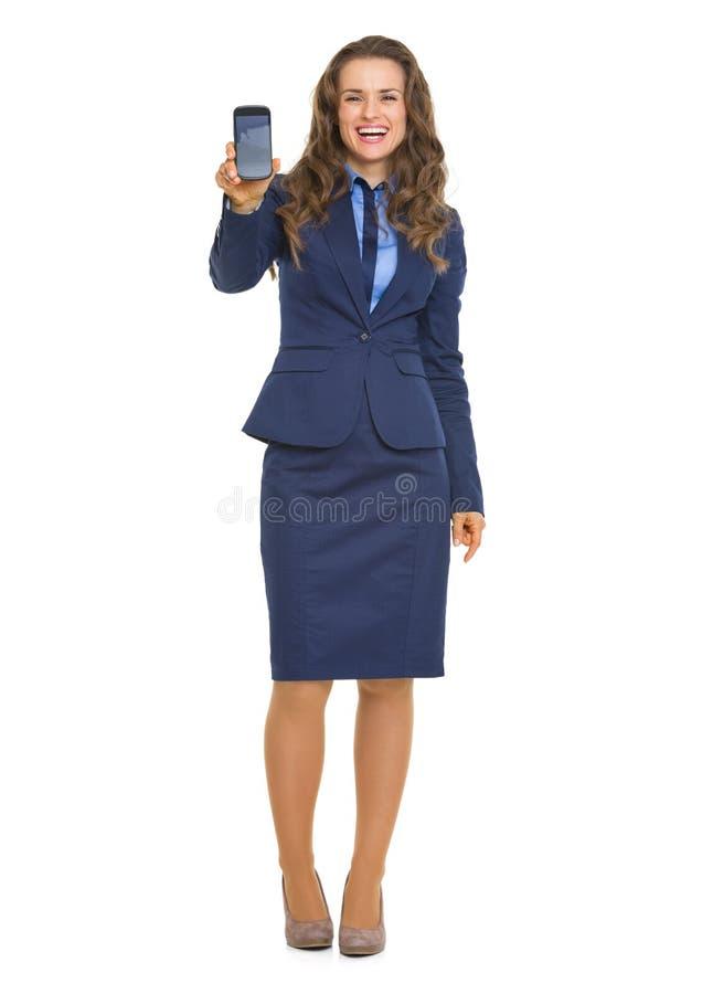 Uśmiechnięta biznesowa kobieta pokazuje telefon komórkowego obrazy stock