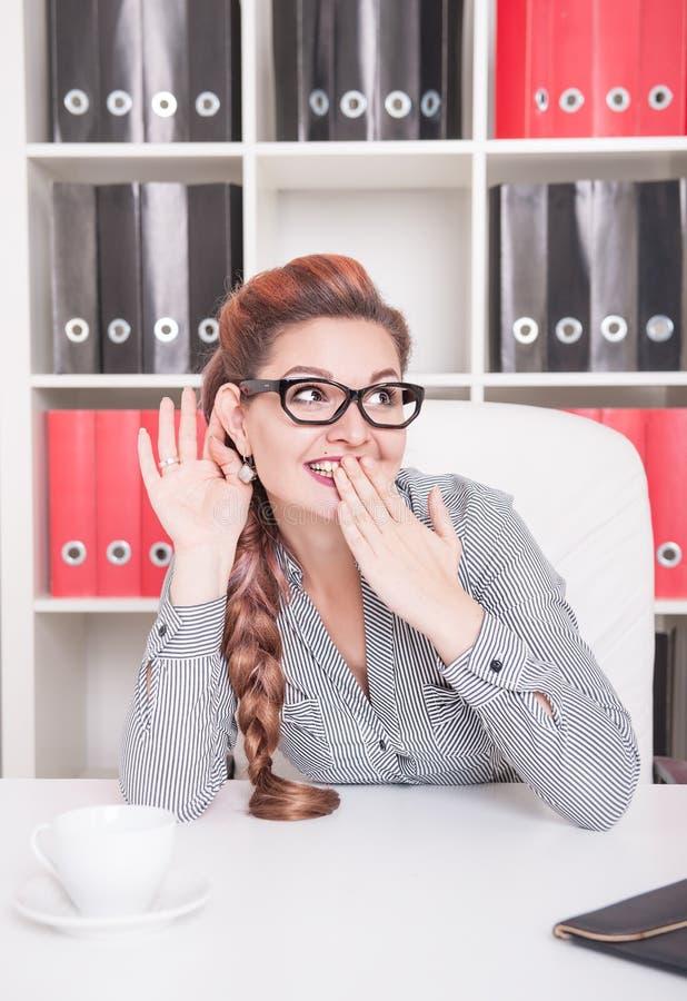 Uśmiechnięta biznesowa kobieta z dużym ucho podsłuchuje zdjęcie stock