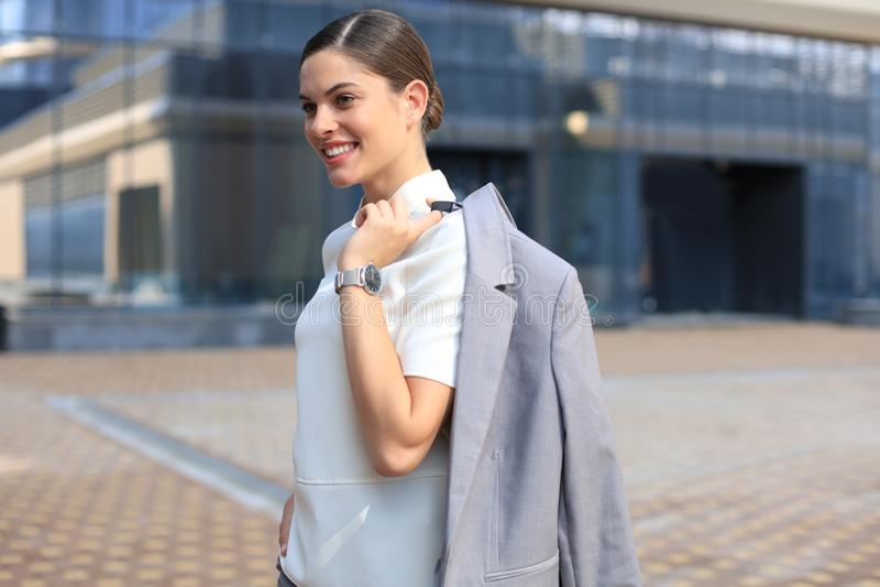 Uśmiechnięta biznesowej kobiety pozycja z kurtką nad jej naramiennym pobliskim budynkiem biurowym obraz stock